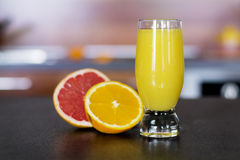 Glass of fresh orange juice on a kitchen countertop Stock Images