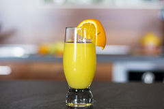 Glass of fresh orange juice on a kitchen countertop Royalty Free Stock Photography
