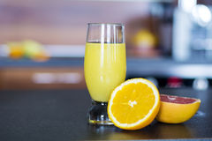 Glass of fresh orange juice on a kitchen countertop Royalty Free Stock Image