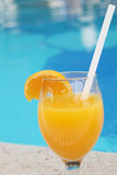 Glass of fresh orange juice near the pool Stock Photography