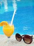 Glass of fresh orange juice near the pool Royalty Free Stock Images