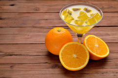 A glass of fresh orange juice and orange on old wooden table. Stock Photography