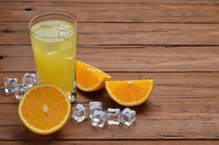 A glass of fresh orange juice and oranges on an old wooden table Royalty Free Stock Images