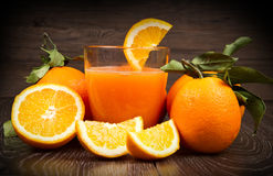 Glass of fresh orange juice and oranges on wooden background Royalty Free Stock Photo