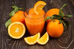 Glass of fresh orange juice and oranges Royalty Free Stock Photo