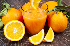 A glass of fresh orange juice and oranges on wooden background Royalty Free Stock Images