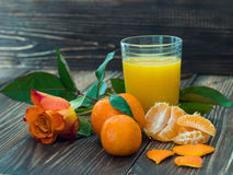 Glass of fresh orange juice and rose on wooden table. Stock Image