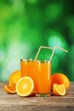 Glass of fresh orange juice on wooden background Stock Image