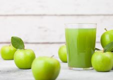 Glass of fresh organic apple juice with granny smith and british bramley apples in box on wooden background with sun light Stock Image
