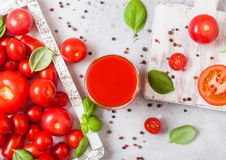 Glass of fresh organic tomato juice with fresh raw tomatoes basil and pepper in box on stone kitchen background royalty free stock photography