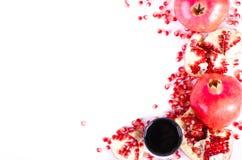 Glass of fresh pomegranate juice and ripe fruit, seeds isolated Stock Image