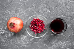 Glass of fresh red pomegranate juice and sliced fruit with seeds dark background top view Royalty Free Stock Image