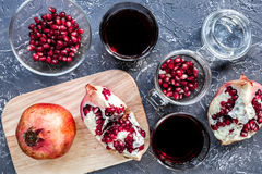 Glass of fresh red pomegranate juice and sliced fruit with seeds dark background top view Stock Photography