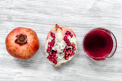 Glass of fresh red pomegranate juice and sliced fruit with seeds gray background top view Royalty Free Stock Photography