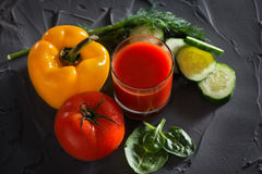 A glass of fresh vegetable juice and vegetables - yellow pepper, red tomato, cucumber and greens. View from above Stock Photos