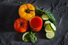A glass of fresh vegetable juice and vegetables - yellow pepper, red tomato, cucumber and greens. View from above Royalty Free Stock Photo