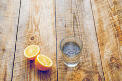 Glass of fresh water with half lemon on wooden table Stock Photo
