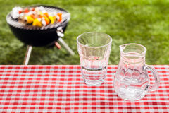 Glass of fresh water with a jug on a picnic table Stock Photography