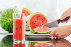 Glass of fresh watermelon juice on table. In kitchen. Young woman slicing a ripe watermelon in background. Healthy eco food rich in vitamins. Popular product of Royalty Free Stock Images