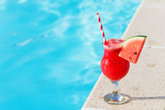 Glass of fresh watermelon smoothie juice drink on border. Of a swimming pool - holiday tropical concept Stock Images