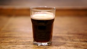 Glass of freshly brewed black coffee. On rustic wooden table Royalty Free Stock Photography