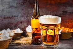 Glass with freshly poured beer and head of foam near bottle and. Plates with snacks on dark wooden desk. Food and beverages concept Royalty Free Stock Photo