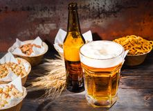 Glass with freshly poured beer and head of foam near bottle and. Plates with pistachios, small pretzels, peanuts on dark wooden desk. Food and beverages concept Stock Photo