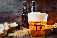 Glass with freshly poured beer and large head of foam near bottl. Es, wheat and plates with snacks on dark wooden desk. Food and beverages concept Stock Photos