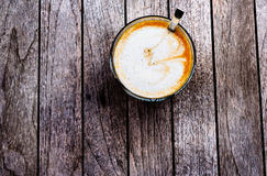 Glass of freshly prepared cortado. With milk foam on a wooden table Stock Photography