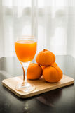 Glass of freshly pressed orange juice with four orange Stock Photography