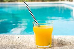 Glass of freshly pressed tropical fruits orange juice with striped straw standing on deck of swimming pool. Bright sunlight. Summer vacation relaxation travel royalty free stock image