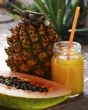 Glass of freshly squeezed juice with drinking straw and ripe pineapple and papaya tropical fruits on wooden table in the garden. Healthy food,diet or vegan food Stock Photos