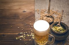 Glass of frothy beer, malt and hop. Cold foam beer with malt grain, green hop leaves in the pots and rye ears on burlap cloth on brown wooden table background stock photo