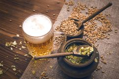 Glass of frothy beer, malt and hop. Cold foam beer with malt grain, green hop leaves in the pots and rye ears on burlap cloth on brown wooden table background stock photography