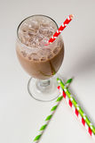 Glass of frothy chocolate milk with red paper straw Stock Photography