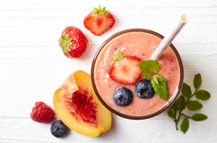 Glass of fruit and berry smoothie. On white wooden background from top view Royalty Free Stock Image