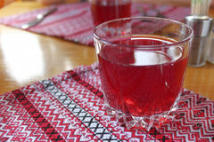 A glass of fruit drink. On an embroidered napkin Stock Images