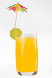 Glass of fruit juice lime slice and umbrella Royalty Free Stock Images
