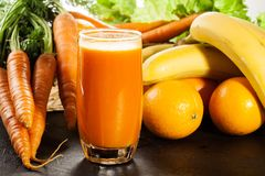 Glass of fruit juice with orange, carrots and banana Stock Image