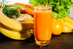 Glass of fruit juice with orange, carrots and banana stock photos