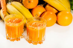 Glass of fruit juice with orange, carrots and banana Royalty Free Stock Photo