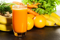 Glass of fruit juice with orange, carrots and banana Royalty Free Stock Photography