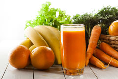 Glass of fruit juice with orange, carrots and banana royalty free stock image