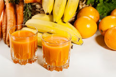 Glass of fruit juice with orange, carrots and banana royalty free stock photos