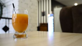 Glass of fruit juice on  table in a cafe stock footage