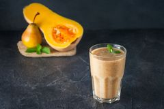 Glass of fruit pear-pumpkin smoothie with mint leaves and ingridients on the dark background. Healthy, vegetarian, vegan diet food. Selective focus, space for Royalty Free Stock Photo