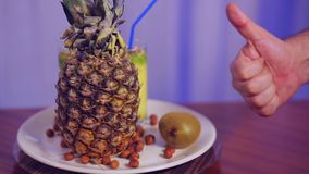 A glass with fruit smoothie on a white plate with fruit and nuts and a gesture class. The average plan stock footage