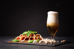 A glass full of beer and foam, pistachios and prosciutto seasoned with pepper and basil on a dark background. Snack for Stock Images