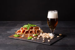 A glass full of beer with foam, pistachios and prosciutto seasoned with pepper and basil on a dark background. Snacks Royalty Free Stock Image