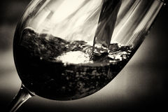 Glass of full bodied red wine being poured. From bottle Royalty Free Stock Photo